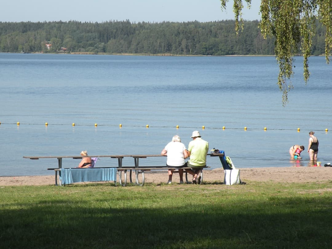 A group of people sitting on a bench next to a body of water