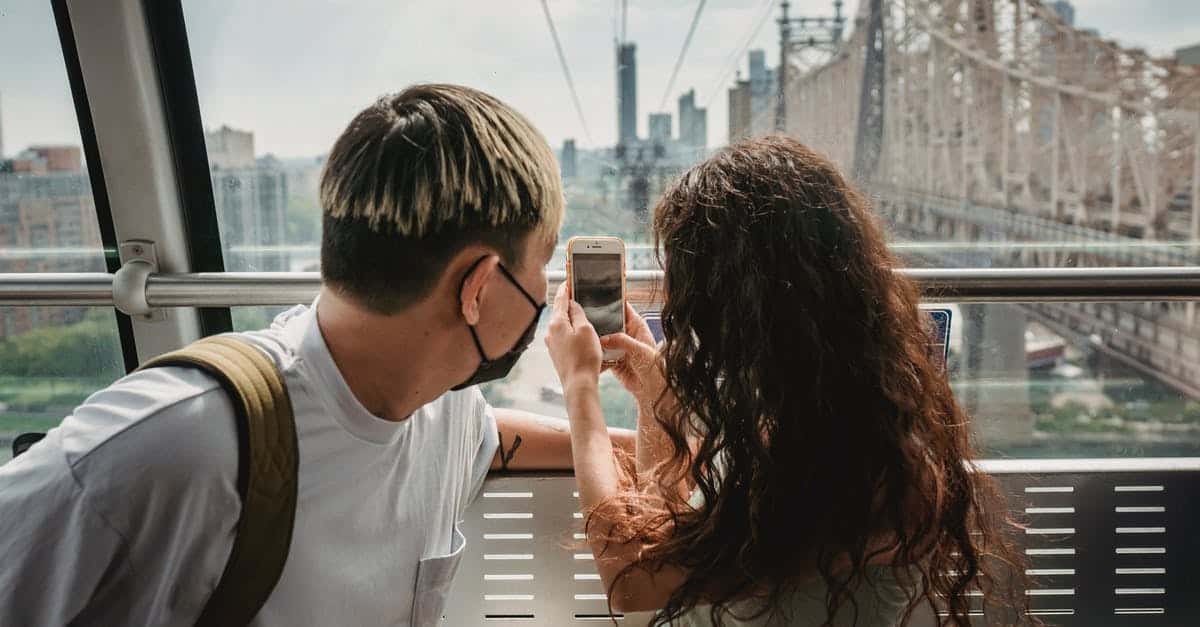 A man and a woman looking at her cell phone